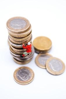 Miniatuur klimmer die op de stapel muntstukken beklimt