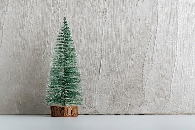 Miniatuur kunstmatige kerstboom zonder versieringen op lichte achtergrond. ruimte kopiëren