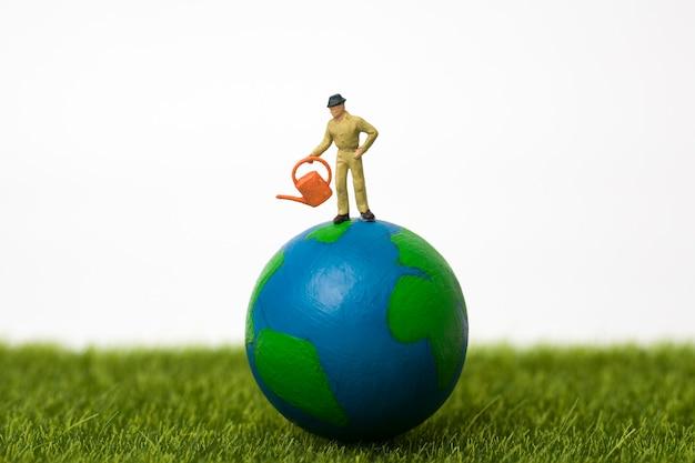 Miniatuur landbouwer die zich op bol op wit bevindt