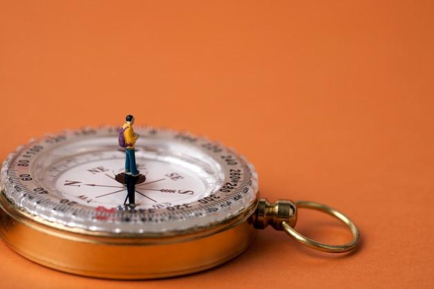 Miniatuur man die op een kompas