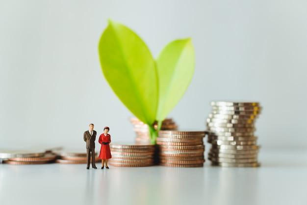 Miniatuur man en vrouw die zich op blad met de achtergrond van stapelmuntstukken bevinden