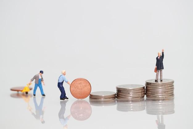 Miniatuur mensen: arbeider met muntstuk en zakenman, bedrijfsconcept die als achtergrond gebruiken