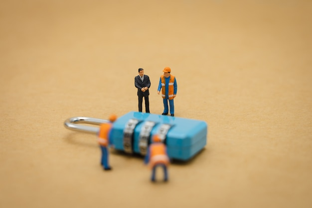 Miniatuur mensen bouwvakker beveiligingssleutel reparatie en de behandeling