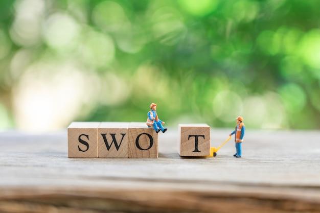 Miniatuur mensen bouwvakker met houten woordteam