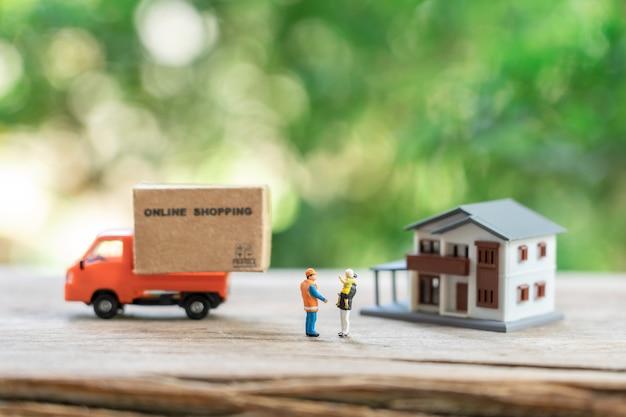 Miniatuur mensen bouwvakker online winkelen met een winkelwagentje en winkelen