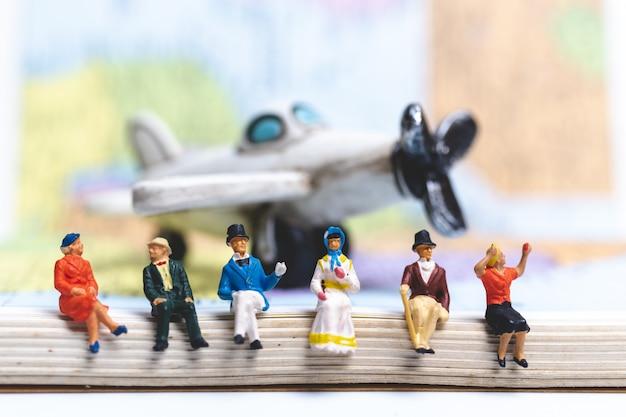 Miniatuur mensen die op het vliegtuig met de achtergrond van de wereldkaart zitten