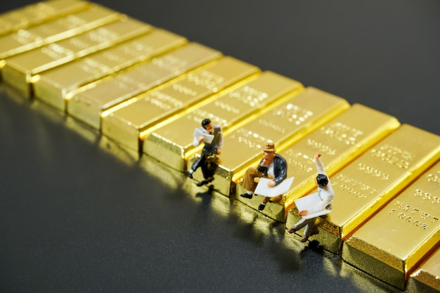 Miniatuur mensen die op stapel van goudstaaf op zwarte achtergrond zitten