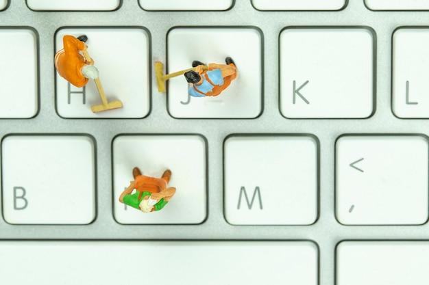 Miniatuur mensen die witte toetsenbordcomputer schoonmaken.