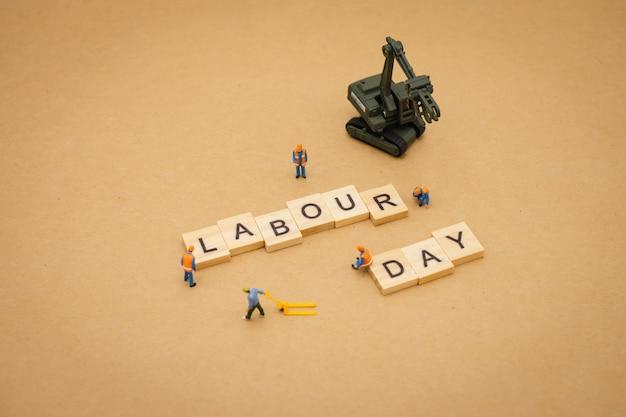 Miniatuur mensen die zich met de houten dag die van de woordarbeid bevinden als achtergrond universele dag gebruiken
