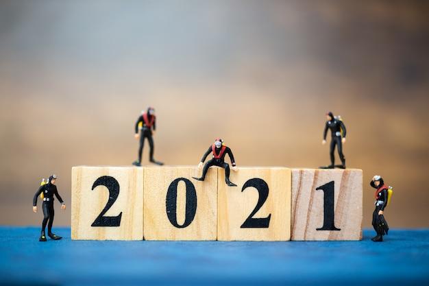 Miniatuur mensen duikers duiken rond houten blok 2021, gelukkig nieuwjaar concept
