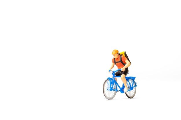 Miniatuur mensen fietskoerier met pakketdoos op de rug geïsoleerd op een witte achtergrond, express levering serviceconcept