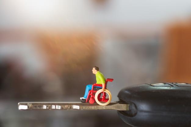 Miniatuur mensen gehandicapte man zit in een rolstoel