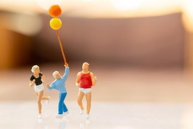 Miniatuur mensen gelukkige familie rennen en spelen met ballon, kindertijd en familie concept.