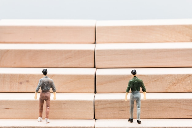 Miniatuur mensen kleine cijfers zakenlieden lopen trap houten podium