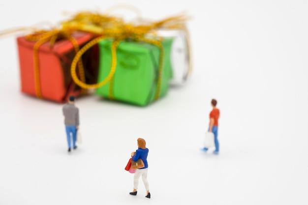 Miniatuur mensen kopen goederen of koopwaar tijdens grootverkoop en korting