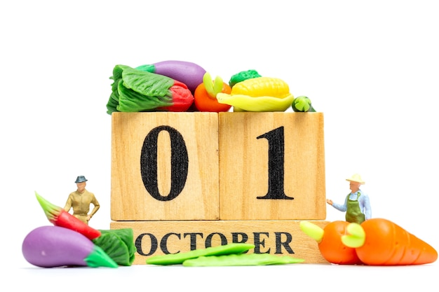 Miniatuur mensen landbouw bezig met hout kalender 1 oktober op witte achtergrond. wereld vegetarisch dag concept