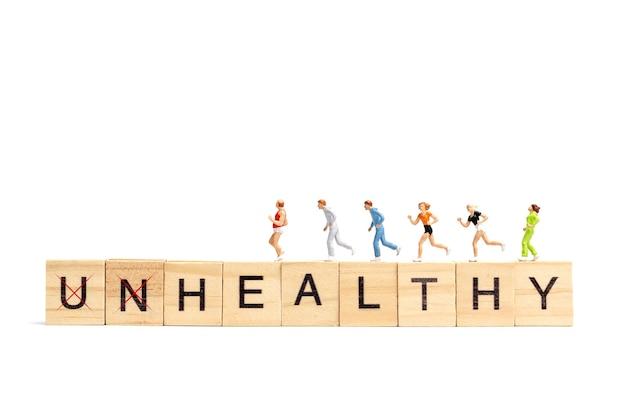 Miniatuur mensen lopen op houten brievenblok op witte achtergrond. gezond concept