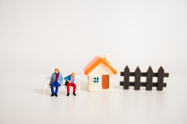 Miniatuur mensen, man en vrouw om thuis te zitten met behulp van als gezinsleven concept