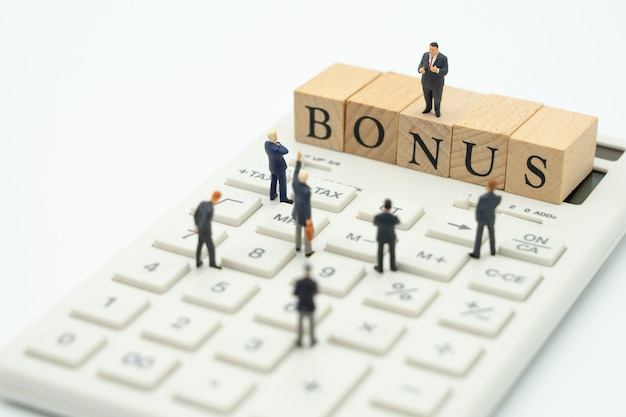 Miniatuur mensen ondernemers die wachten op winst winsten van het bedrijf om een bonus te betalen.