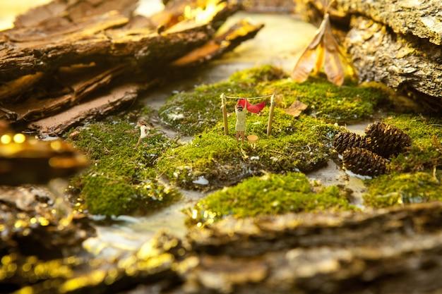 Miniatuur mensen op de achtergrond van mos en schors