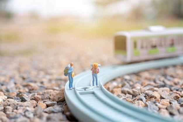 Miniatuur mensen: paar backpacker die op de spoorweg loopt
