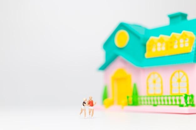 Miniatuur mensen, paar loopt samen in de buurt van hun huis, gezonde levensstijl concept