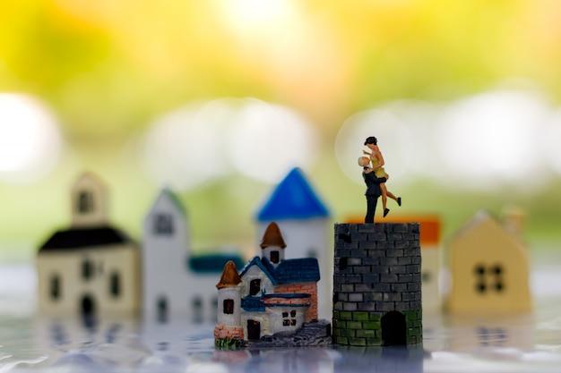 Miniatuur mensen paar minnaar staande op kasteel en kleine huis.