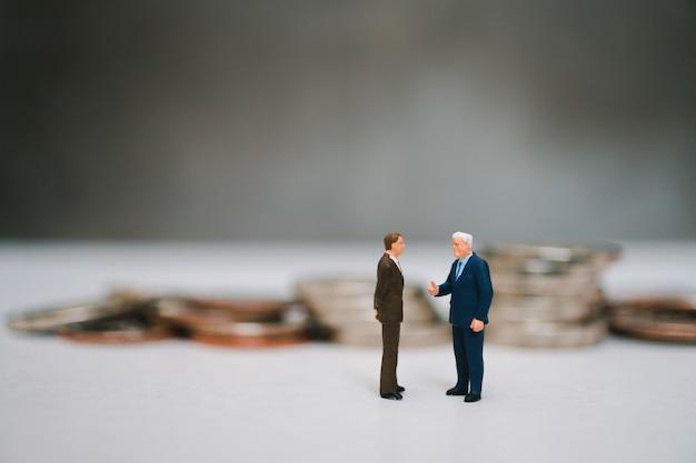 Miniatuur mensen, paar zakenman staande op stapel munten achtergrond