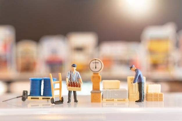 Miniatuur mensen postbode officier van dienst, hij bereidt zich voor om een doos naar de consument te sturen. bezorgservice voor e-commerce concept Premium Foto