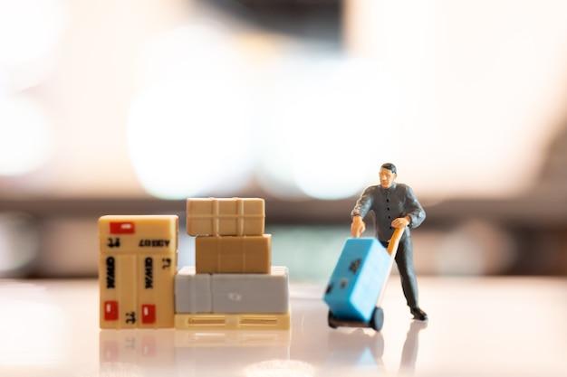 Miniatuur mensen postbode officier van dienst, hij bereidt zich voor om een doos naar de consument te sturen. bezorgservice voor e-commerce concept