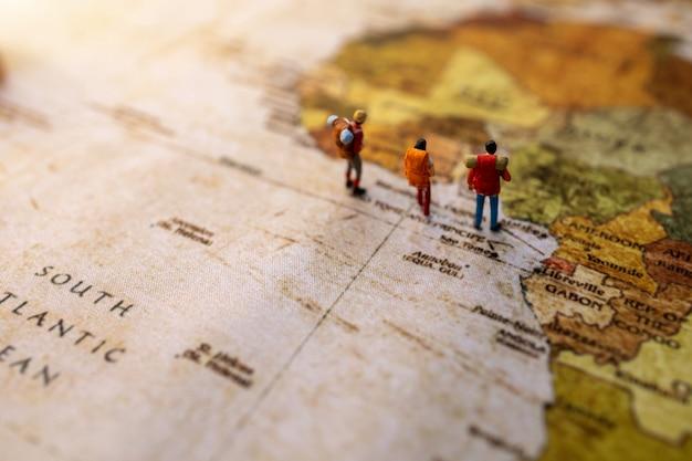 Miniatuur mensen: reizen met een rugzak staande op vintage wereldkaart, reizen en zomer concept.