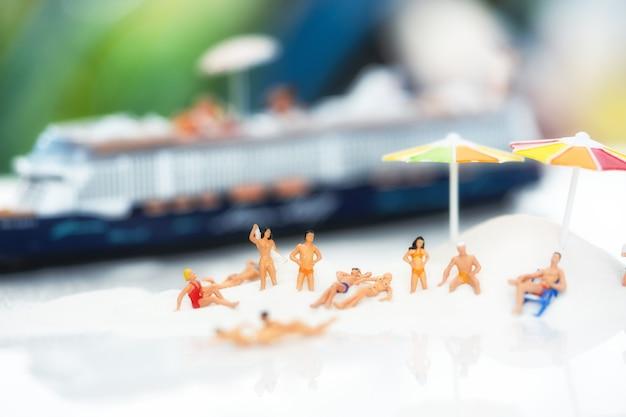 Miniatuur mensen, reizigers die op de zandbak ontspannen die in de zomerthema versieren