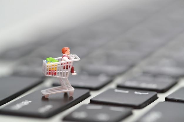 Miniatuur mensen: shoppers drukken op het computertoetsenbord als betaalmethode online vanuit huis