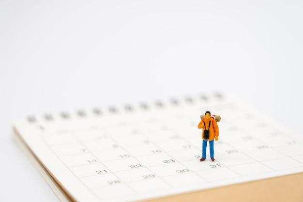 Miniatuur mensen staan op een boekenranglijst (lijst) het begin van de reis