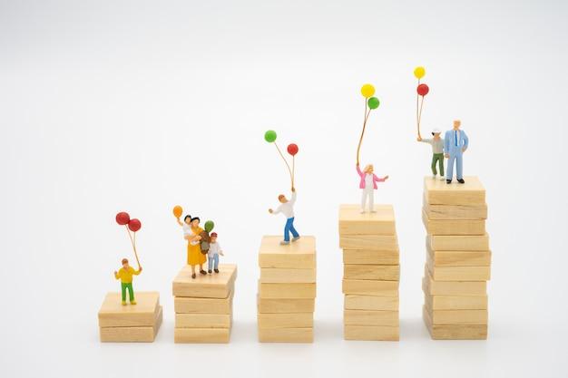 Miniatuur mensen staan op papier stapels met ballonnen