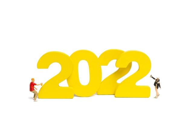 Miniatuur mensen tiener spuiten verf nummer 2022 op witte achtergrond, gelukkig nieuwjaar concept