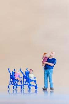 Miniatuur mensen vader met hun schattige babydochter in de armen Premium Foto