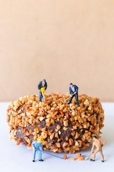 Miniatuur mensen werkend team dat zelfgemaakte chocolade butternut donuts maakt
