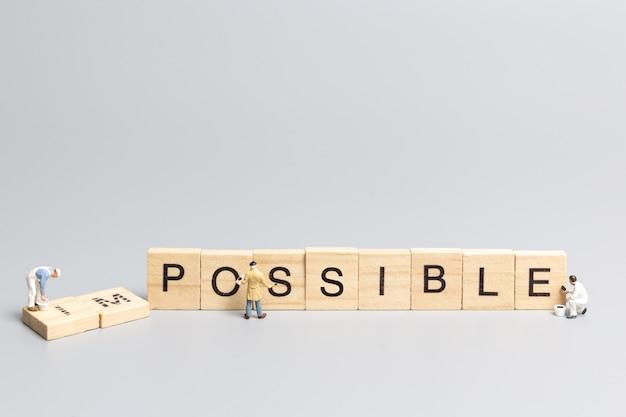Miniatuur mensen werknemer team op onmogelijk woord in houten alfabet letters met voorvoegsel un doorgestreept, waardoor het woord mogelijk blijft