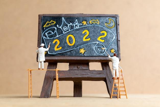 Miniatuur mensen werknemer team schilderij nummer 2022 op zwart bord, gelukkig nieuwjaar concept