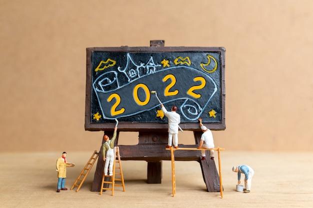 Miniatuur mensen werknemer team schilderij nummer 2022 op zwart bord, gelukkig nieuwjaar concept Premium Foto