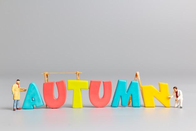 Miniatuur mensen werknemer team schilderij van de herfst met plaats voor tekst op grijze achtergrond, hallo herfst concept