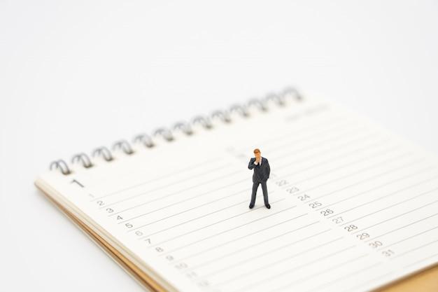 Miniatuur mensen zakenlieden analyseren staande op een boek ranglijst (lijst).
