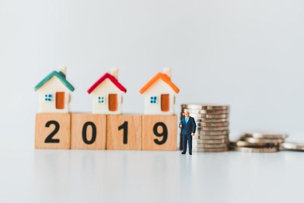 Miniatuur mensen, zakenman die zich met mini-huis op houten blok 2019 en stapel munten