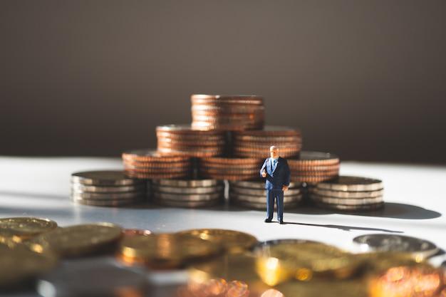 Miniatuur mensen, zakenman die zich op de achtergrond van stapelmuntstukken bevinden