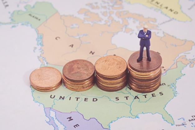 Miniatuur mensen, zakenman die zich op de kaart amerikaanse