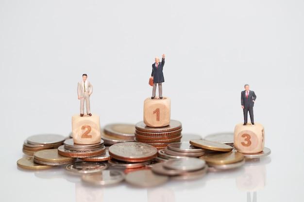 Miniatuur mensen: zakenman die zich op het stapelen van munten bevindt
