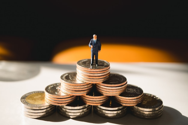 Miniatuur mensen, zakenman die zich op stapel van munten