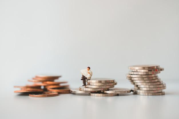 Miniatuur mensen, zakenman krant lezen op stapel munten