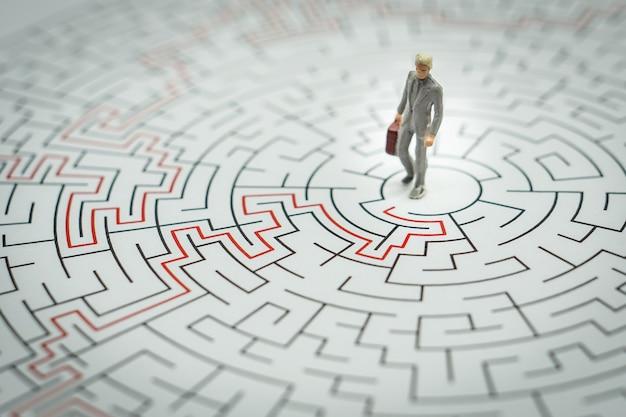 Miniatuur mensen zakenman lopen in een doolhof.